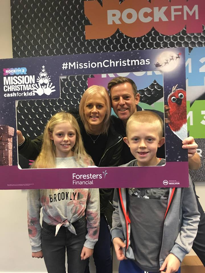 Radio presenters posing with two young children inside a cardboard picture frame promoting Foresters Financial and Mission Christmas