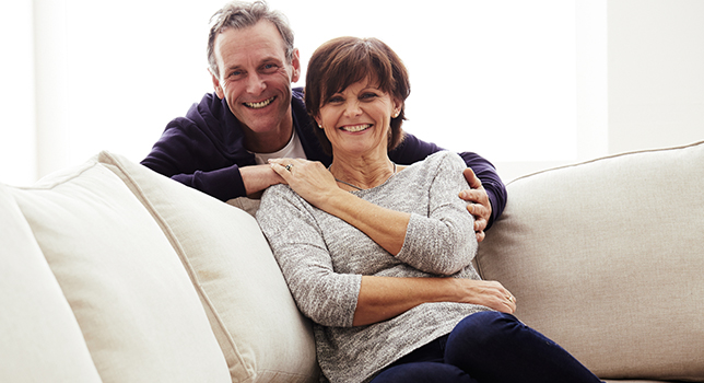 happy mature couple holding hands on couch