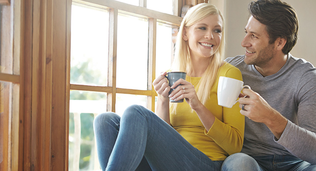 happy couple enjoying cups of coffee in front of sunny window