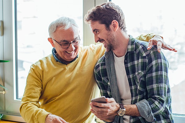 Happy father and son requesting a Financial Adviser on their mobile