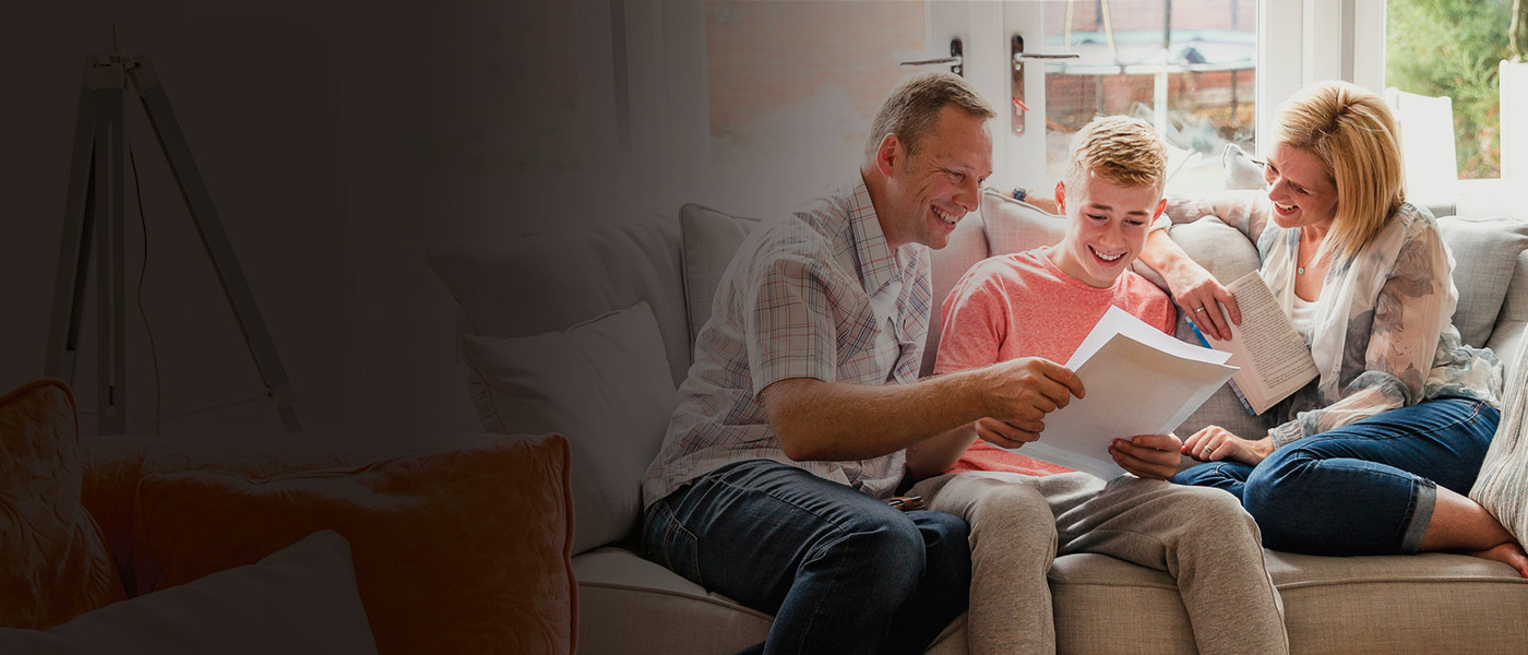 Teenager with his parents learning about his Foresters savings Plan at 18 on their sofa