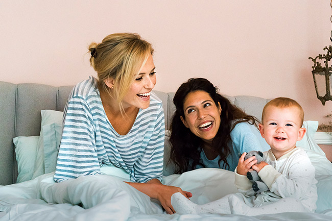 Happy mums sitting on bed after contributing to their child's Junior ISA