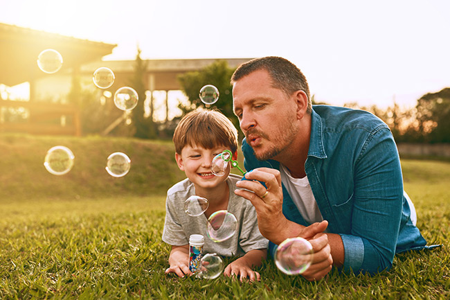 Father and son blowing bubbles in the garden