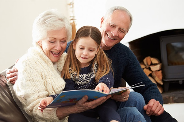 Grandparents reading a book who have a MyPlans gifter account for their daughter