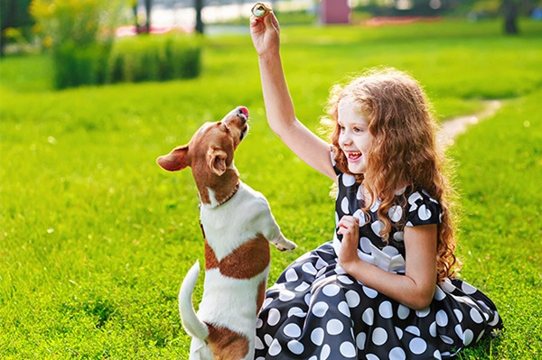 Girl playing with her dog who has a Foresters children's savings Plan
