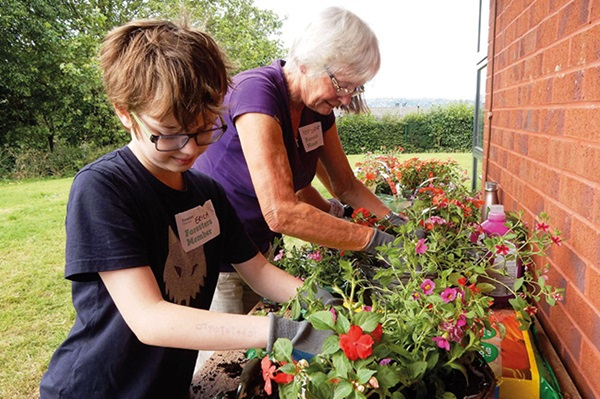Foresters member and grandson planting flowers at a member event