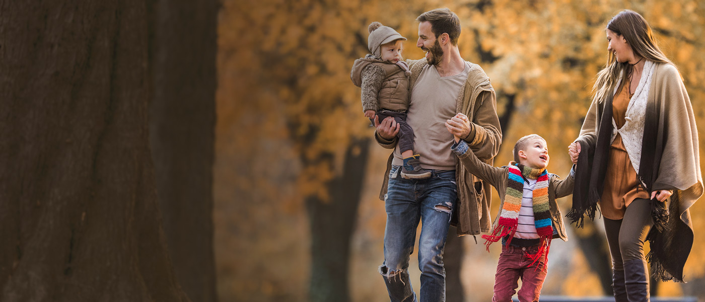 Happy family walking in woods care free covered with Forester Life Protection Plan