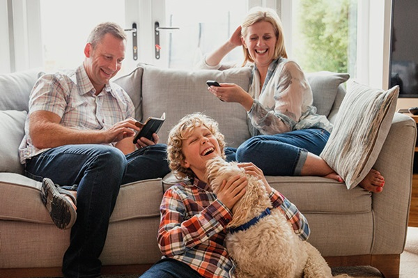 Happy family sitting on sofa with Foresters personal insurance