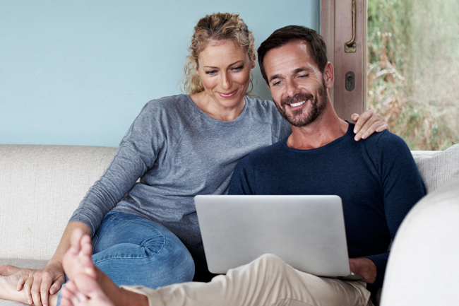 Happy husband and wife checking their MyPlans account on a laptop