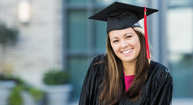 smiling female college graduate wearing graduation cap and gown