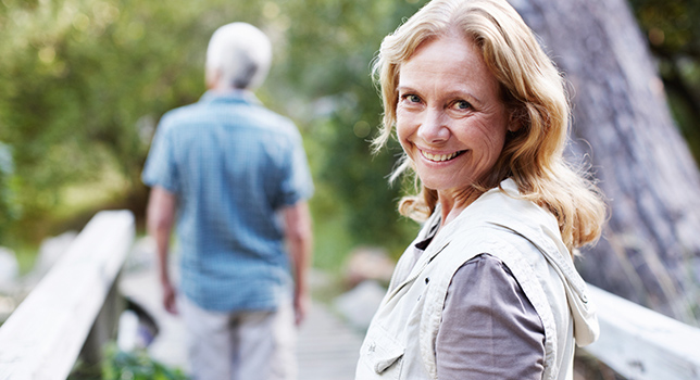 Woman smiling towards camera while man walks across bridge