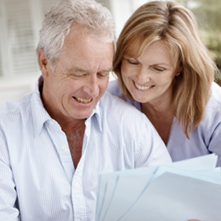 elderly couple reading papers together